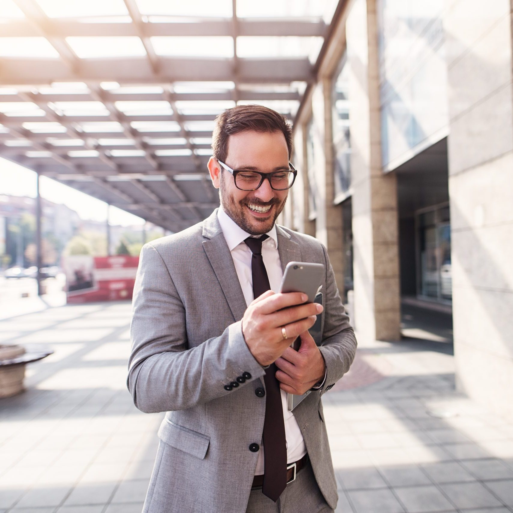 Say yes to a good job.Happy businessman in suit walking to his office and checking his mail on cell phone.